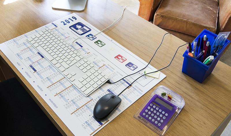 Impression calendrier remborde sous main bureau